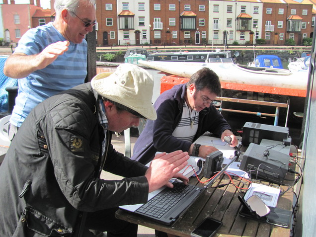 Henryk M0HTB operating GB0CCC with Julian M0JCE logging. Eddie M0LJT observes and shades the laptop screen from the sun